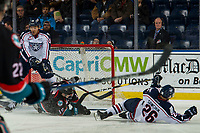 KELOWNA, CANADA - DECEMBER 5: Dalton Gally #3 of the Kelowna Rockets slides into the net as Aaron Hyman #38 of the Tri-City Americans attempts to block a shot on December 5, 2018 at Prospera Place in Kelowna, British Columbia, Canada.  (Photo by Marissa Baecker/Shoot the Breeze)
