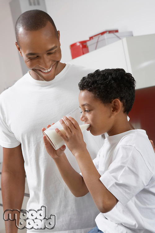 Father watching son (7-9) drinking milk, indoors
