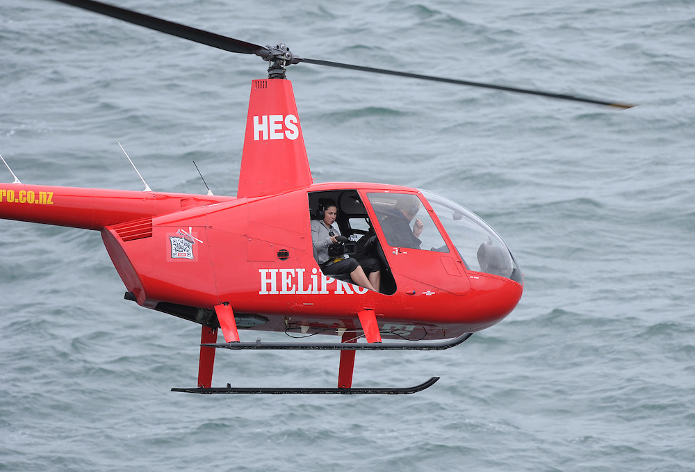 A TV film crew in a Helipro Robinson helicopter hover over race six of the New Zealand Offshore Powerboat Championships, Wellington Harbour, Wellington, New Zealand, Saturday, April 14, 2012. Credit:SNPA / Ross Setford