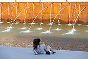 Young woman in a time to break along one of the canals of Expo 2015 with water jets and fountains, Rho-Pero Milan in June 2015. &copy; Carlo Cerchioli<br /> <br /> Una giovane donna in un momento di sosta lungo uno dei canali all'Expo 2015 con getti d'acqua e fontanelle, Rho-Pero, Milano giugno 2015.