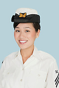 Portrait of a young beautiful US Navy officer smiling over light blue background