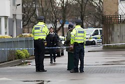 © Licensed to London News Pictures. 02/04/2018. London, UK. Police officers at the crime scene on the estate behind a parade of shops on the A12 in Bromley by Bow, E3 where a teenager was stabbed last night at around 6:05pm. A 16 year old boy suffering stabbing injuries and also a further victim were taken to an east London hospital by London Ambulance staff. The teenage victim remains in a critical condition this morning. Photo credit: Vickie Flores/LNP