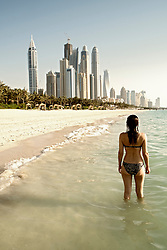 Woman standing on beach with skyline of towers to rear in Dubai United Arab Emirates
