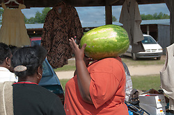 Woman holding a watermelon at a flea market