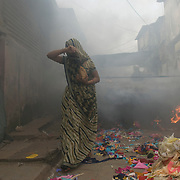 A woman walks through the smoke from the burning kilns at Kumbharwada, the potter's colony. The kilns are fed with waste fabric bought from the tailors.