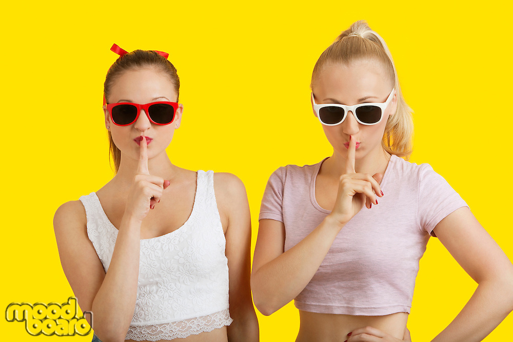 Portrait of two playful young women with fingers on lips over yellow background