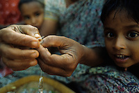 A mother is making a necklace for her daughter, carefully putting each bead onto the thread.