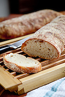 Sliced Ciabatta bread on a wooden cutting board with a bread knife. A second loaf of bread is visible in the background.