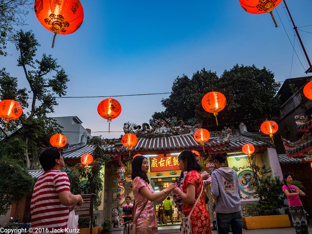 "08 FEBRUARY 2016 - BANGKOK, THAILAND: People go into a small shrine in Bangkok's Chinatown district during the celebration of the Lunar New Year. Chinese New Year is also called Lunar New Year or Tet (in Vietnamese communities). This year is the ""Year of the Monkey."" Thailand has the largest overseas Chinese population in the world; about 14 percent of Thais are of Chinese ancestry and some Chinese holidays, especially Chinese New Year, are widely celebrated in Thailand.       PHOTO BY JACK KURTZ"