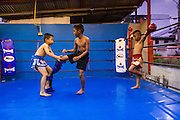 "17 DECEMBER 2104 - BANGKOK, THAILAND: The Kanisorn boxing gym is a small gym along the Wong Wian Yai - Samut Sakhon train tracks. Young people from the nearby communities come to the gym to learn Thai boxing. Muay Thai (Muai Thai) is a Thai fighting sport that uses stand-up striking along with various clinching techniques. It is sometimes known as ""the art of eight limbs"" because it is characterized by the combined use of fists, elbows, knees, shins, being associated with a good physical preparation that makes a full-contact fighter very efficient. Muay Thai became widespread internationally in the twentieth century, when practitioners defeated notable practitioners of other martial arts. A professional league is governed by the World Muay Thai Council. Muay Thai is frequently seen as a way out of poverty for young Thais and Muay Thai camps and schools are frequently crowded. Muay Thai professionals and champions are often celebrities in Thailand.     PHOTO BY JACK KURTZ"