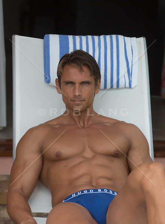 sexy man sitting in a lounge chair