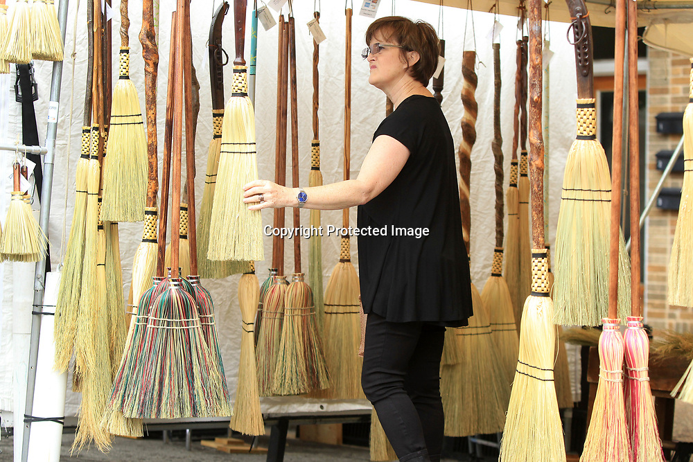 Barb Letourneau, from Columbus, looks over the variety of brooms on display at George Jones Jr.'s tent at the GumTree Arts Festival Saturday in Tupelo. Jones is broommaker based in Florence Alabama.