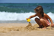 Young girl plays in the sand on a beach