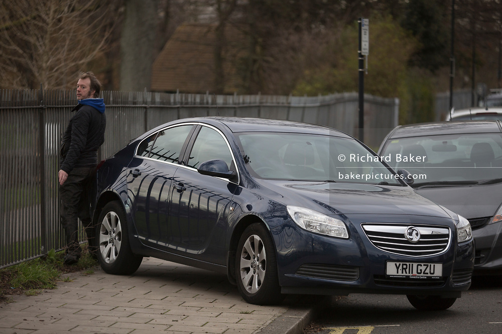 A person squeezes past a mysteriously abandoned Vauxhall car resting at 45 degrees, off the road but blocking a pavement on Ruskin Park, on 2nd February 2018, in Southwark, London, England.