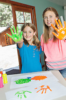 Portrait of sisters with paint covered hands and colorful handprints on papers