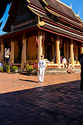 A woman and others take in the sights of one of Vientiane's many beautiful temples, Vientiane, Laos.