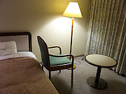 hotel room at night with one chair facing the window