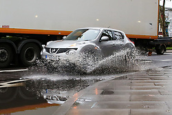 © Licensed to London News Pictures. 14/10/2019. London, UK. A car drives through a large puddle of water left on Tottenham High Road after heavy overnight rainfall in north London. According to the Met Office more than two inches of rain could fall this afternoon. Photo credit: Dinendra Haria/LNP