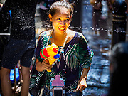 13 APRIL 2018 - BANGKOK, THAILAND:  A woman gets hit with a squirt gun during a water fight on Silom Road during the first day of Songkran in Bangkok. Songkran is the traditional Thai New Year celebration best known for water fights.   PHOTO BY JACK KURTZ