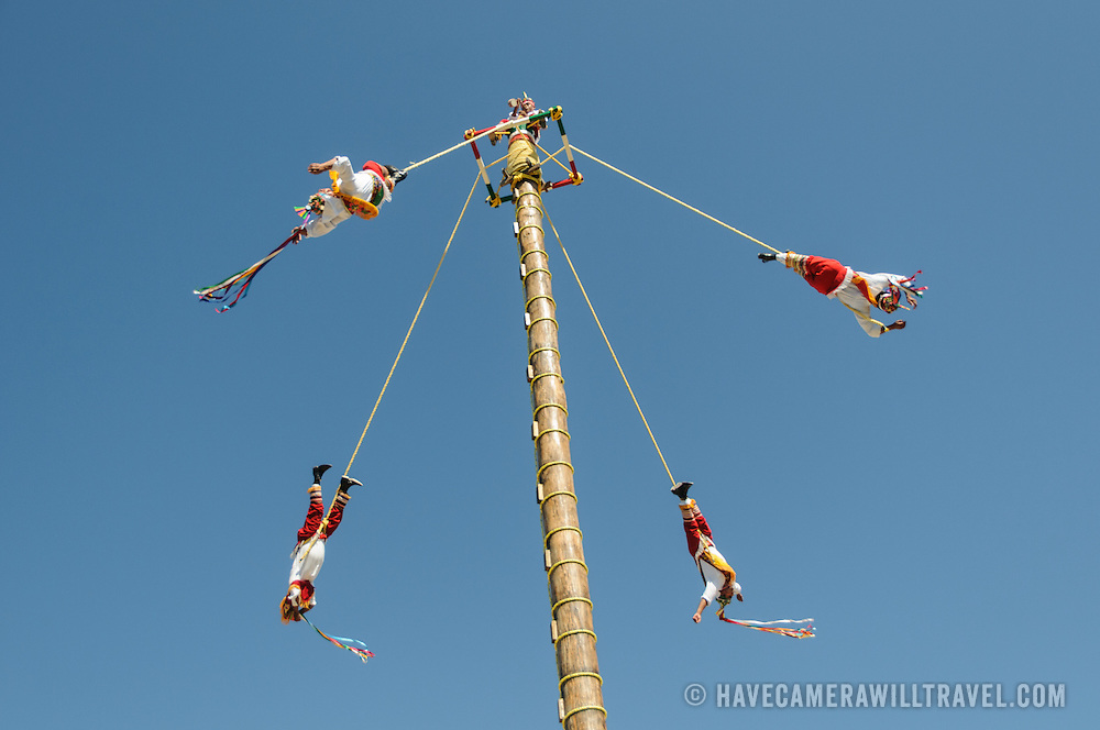Five performers (one playing a pipe musical instrument sitting on the apex) perform a traditional Mayan rope ceremony swinging from a very tall pole at the Xcarat Park complex on Mexico's Yucatana Peninsula not far from Tulum.