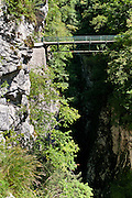 "Devil's Bridge carries an autombile road across Tolmin gorges/Tolminska korita, in Triglav National Park, Zatolmin, Slovenia, Europe. Walk a trail along Tolminka river gorge, starting at the parking lot at the Triglavski narodni park (TNP) sign, near Zatolmin in the Julian Alps. Loop upwards to the scenic Devil's Bridge (""Hudicev most,"" built 1907), which carries Tolmin-Cadrg road sixty meters above Tolminka River. Tolmin gorges (Tolminska korita) are among the longest and deepest gorges in Slovenia and are the lowest point (180 meters elevation) in Triglav National Park (TNP)."