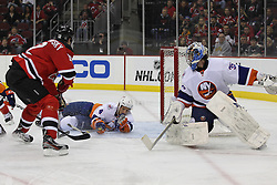 Apr 3; Newark, NJ, USA; New York Islanders defenseman Mark Eaton (4) makes a sliding save on New Jersey Devils left wing Alexei Ponikarovsky (12) during the second period at the Prudential Center.
