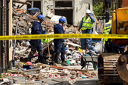 © Licensed to London News Pictures. 29/06/2012. Oldham , UK . A large explosion , believed to be caused by gas , has brought down at least one house in an Oldham terrace. Search and rescue teams and other investigating teams painstakingly pick through the destruction for clues and recoverable property . Photo credit : Joel Goodman/LNP