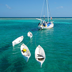 A flotilla of small conch boats used by traditional fisherman at anchor inside to the barrier reef off of Belize.