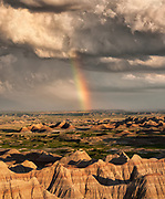 Most of the rainfall in the Badlands region falls in the period from May to July, often in the form of powerful storms, sometimes loosely referred to as monsoons. If the storms occur, the light on the landscape can be dramatic, often with rainbows being formed. Badlands National Park in South Dakota, USA.