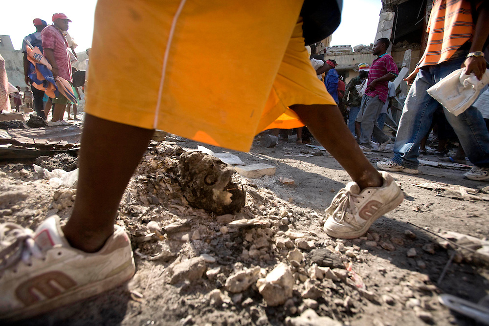 Woman passing next to burnt dead body  in downtown Port-au-Prince after the earthquake in Haiti on January 18, 2010.