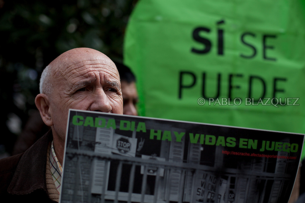 An Anti-eviction activist demonstrates claiming the vote for a Popular Legistative Initiative (ILP) to stop evictions, regulate dation in payment and social rent outside the Municipal Building of Vallecas, which is office of Popular Party (PP) deputy Eva Duran, on April 3, 2013 in Madrid, Spain. Placard reads 'Yes we can' and 'There are lives at risk'. The Mortgage Holders Platform (PAH) and other anti evictions organizations are organizing 'escraches' since several weeks ago outside Popular Party deputies houses and offices.