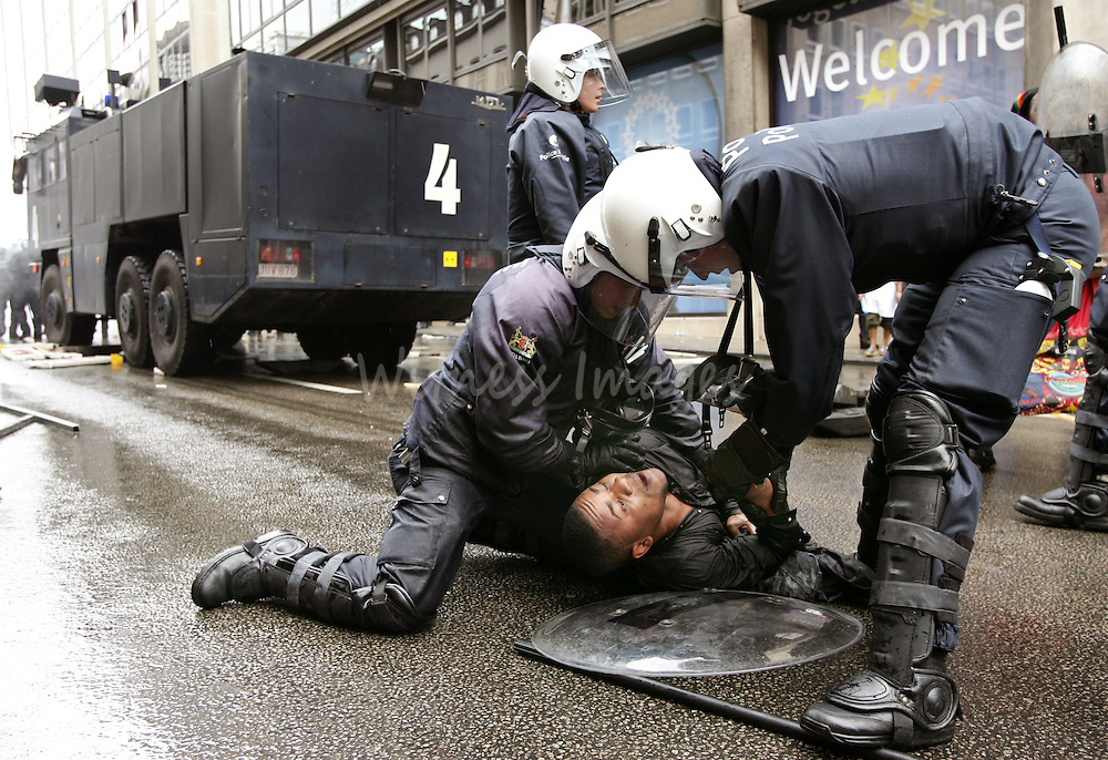 Belgian riot police officers arrest member of Congolese opposition party during a demonstration in Brussels.  Belgian riot police officers arrest a member of a Congolese opposition party during a demonstration in Brussels June 30, 2005. Demonstrators in Belgium protested against the delay of elections in Congo which should have taken place today, the 45th anniversary of the former Belgian colony's independence. REUTERS/Thierry Roge Pictures of the Month June 2005 Pictures of the Year 2005