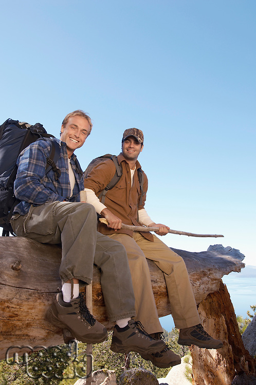 Two male hikers sitting on log (portrait)