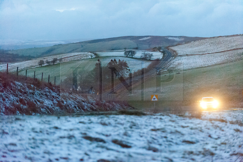 © Licensed to London News Pictures. 10/03/2019. Builth Wells, Powys, Wales, UK. A motorist drives along the B4520 between Brecon and Builth Wells through a wintry landscape on the Mynydd Epynt moorland in Powys, Wales, UK. After a day of  sunny spells, bitterly cold winds, and hailstorms, temperatures dropped to around zero degrees C and snow fell this evening on high land in Powys. Photo credit: Graham M. Lawrence/LNP
