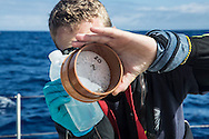 North Atlantic Ocean, October 2014.<br /> Marine biologist Adam Porter rising a sample recovered from a trawl, days away from land, on board the Sea Dragon. &copy; Chiara Marina Grioni