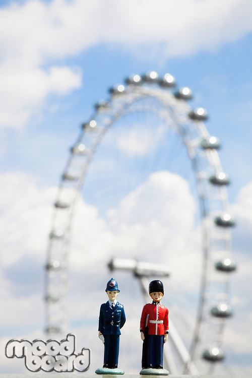 Figurines of police officer and coldstream guard with London Eye in the background