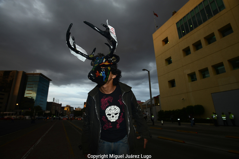 """Mexico City - A young protester wearing a mask of the indigenous mythological spirit """"nahual"""" scares people away from leading presidential candidate Enrique Peña Nieto, the rising telegenic star of Mexico's old PRI party,  during a protest. The rally was organized by the #YoSoy132 movement, which is just forming. (PHOTO: MIGUEL JUAREZ LUGO)"""
