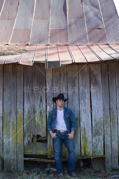 portrait of an All American Cowboy against a wooden barn
