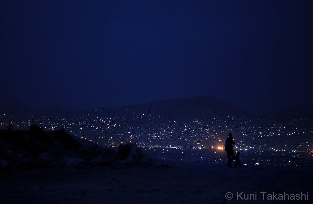 (Kabul Afghanistan - May 9, 2012).A man and child take a walk on top of the hill in Kabul, Afghanistan on May 9, 2012, as city lights illuminate the sky. With an estimated population of 30 million, the war-torn country has been struggling to rebuild while political instability continues. .(Photo by Kuni Takahashi)