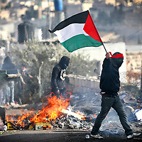 02/01/2009. Clashes in east Jerusalem.........Palestinian protesters burn tires and wave the Palestinian flag during clashes with Israeli troops in East Jerusalem, as they demonstrate against Israel's military operation in Gaza, January 02, 2008. Photo by Michal Fattal. ....