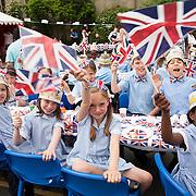 Children waving English flags to celebrate the Diamond Jubilee at Corpus Christi Catholic School. London, 1 June 2012