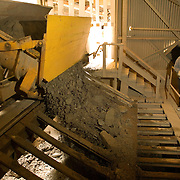 Silver ore is dumped from railcars into a large grizzly which separates the larger rocks. The smaller mixture rides a conveyor belt to the ball mill for further crushing. Larger chunks of ore are broken with a sledge hammer.