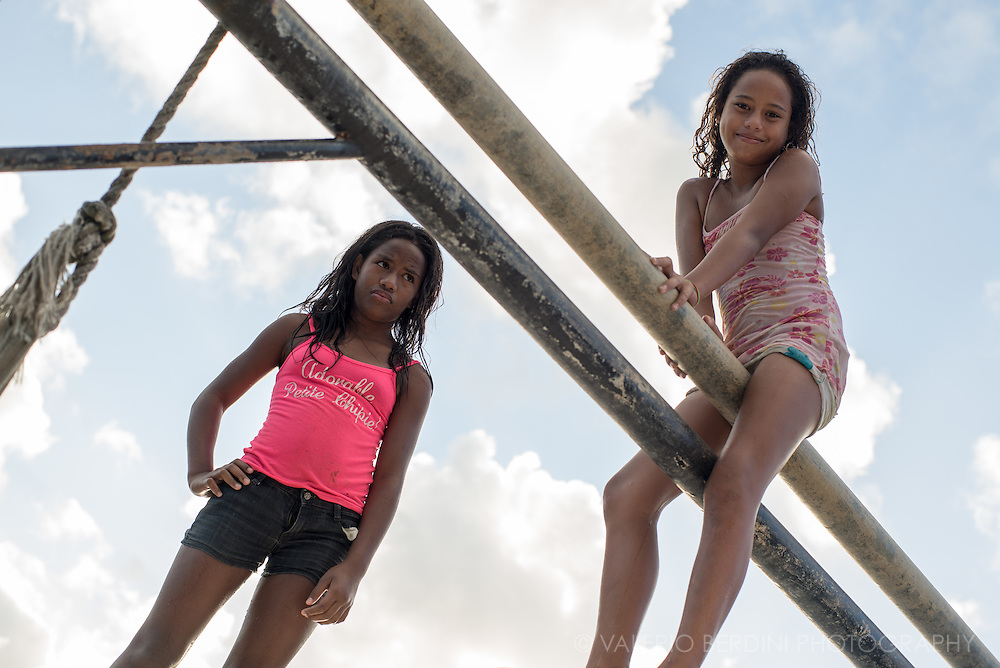 Two girls playing on the pulleys used for beaching the boats in the port of Vaitape in Bora Bora