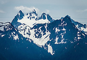Chimney Rock (7726 feet) is on left, Chimney Rock West in middle, and Overcoat Peak on the right. This view is due south from atop Beckler Peak Trail, 7.4 miles round trip with 2200 feet gain, in Mount Baker-Snoqualmie National Forest, Washington, USA. See vistas of the town of Skykomish, Skykomish Valley, and Alpine Lakes Wilderness, Wild Sky Wilderness and Henry M. Jackson Wilderness. Directions: Drive US Highway 2 to near Milepost 52, and turn north onto Forest Service Road 6066. Drive 6.6 miles on a gravel road to the Jennifer Dunn Trailhead.