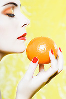 beautiful caucasian woman portrait smelling an orange tangerine fruit  studio on yellow background