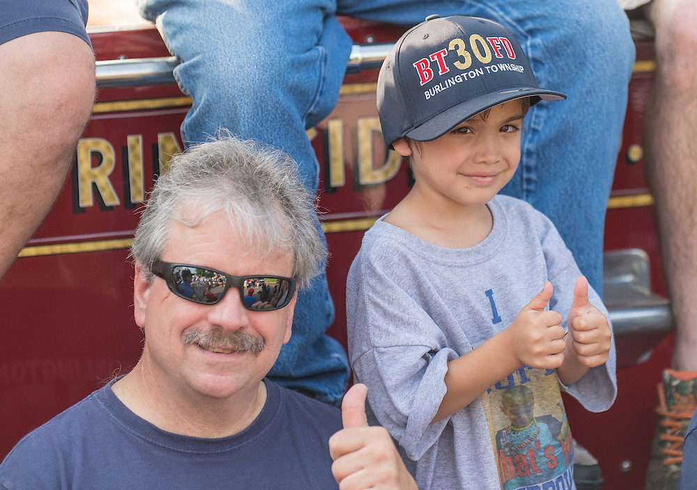 Dominic Mazzio gives two thumbs up with Township Firefighter/Paramedic Tony Coreia during the departments visit to Dominic's birthday party in Burlington Township, NJ, Sunday, June 14, 2015.  Emergency responders, with their police cars and fire trucks, visited the party to honor Dominic and his bravery as he battled childhood diseases.  When Dominic was two, he was diagnosed with Transverse Myelitis, a rare disease in the spinal cord.   After battling that condition for two years, and relearning most of his motor skills, he was diagnosed with inoperable cancer of the brain stem.  A condition unrelated to his first disease, according to doctors.  &ldquo;It was like getting struck by lightening twice&rdquo; said his mother Ashley Mazzio.  In November Dominic endured 30 days of proton radiation, a treatment that has momentarily stopped the growth of the tumor.  He is scheduled for his next doctor&rsquo;s visit in July.  The hope is that no further growth of the tumor is found.  <br /> Photo by Bryan Woolston/@woolstonphoto