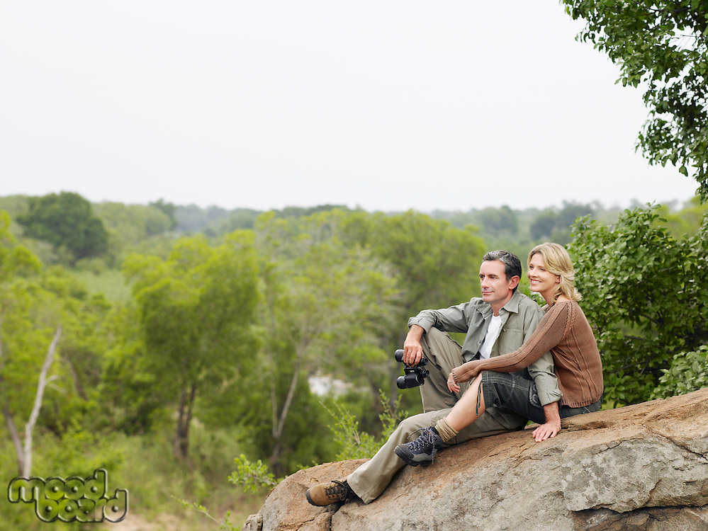 Couple sitting on rock looking at view