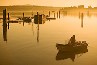 Early morning light creates a dreamy backdrop for a fisherman in his boat, heading out fishing.  Union Bay, Vancouver Island, British Columbia, Canada.