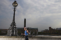 Cyclist carrying bicycle along river embankment side view London England
