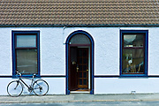 Street scene white pebbledash terraced bungalow and bicycle in Kilkee, County Clare, West of Ireland